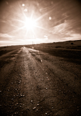 stock-photo-14376329-country-road-leading-into-sun-flare